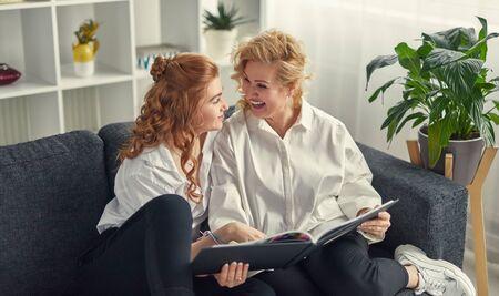 Young and mature women enjoying photo album