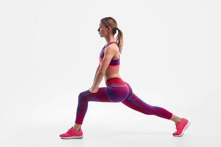 Muscular female lunging during workout Standard-Bild