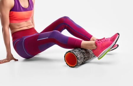 Crop female exercising with foam roller 스톡 콘텐츠