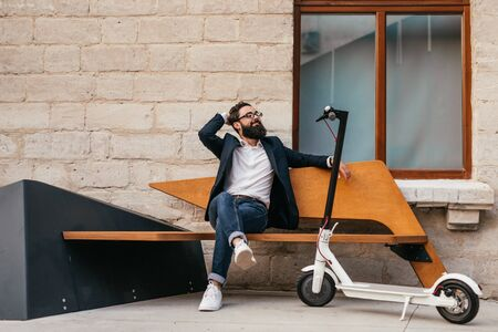 Relaxed hipster sitting on bench near eco vehicle Banque d'images