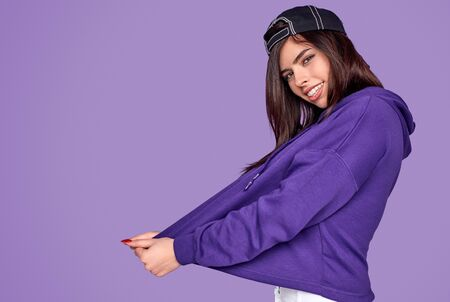 Cheerful young woman in purple hoodie and black cap