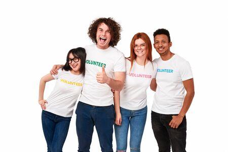 Heureux bénévoles multiraciaux souriant pour la caméra