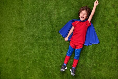 Happy little superhero lying on grass Stock Photo - 128958501