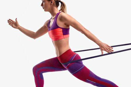 Slim female exercising with resistance band