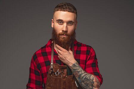 Thoughtful hairdresser touching beard