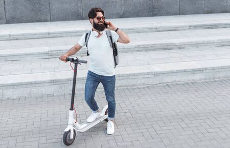 Hipster on electric scooter speaking on smartphone