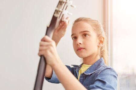 Focused girl tuning guitar