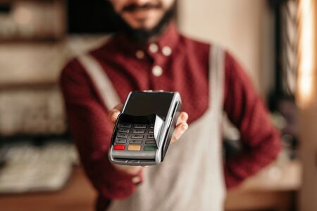 Modern hipster waiter handing over payment terminal in cafe
