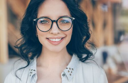 Charming young woman in glasses smiling at camera