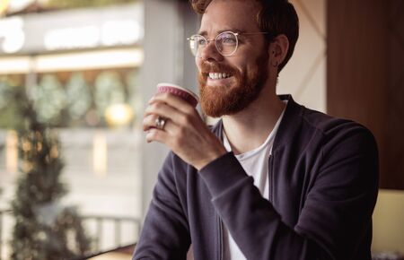 Joyful bearded man with ginger hair drinking coffee at cafe