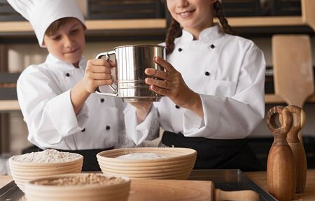Confident children cooks in uniform sifting flour together