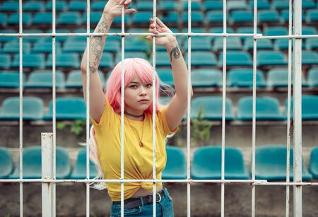 Pink haired Asian woman holding on fence
