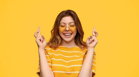 Smiling young woman making wish Banco de Imagens