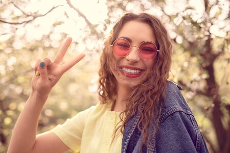 Cheerful trendy woman showing peace sign while standing at park