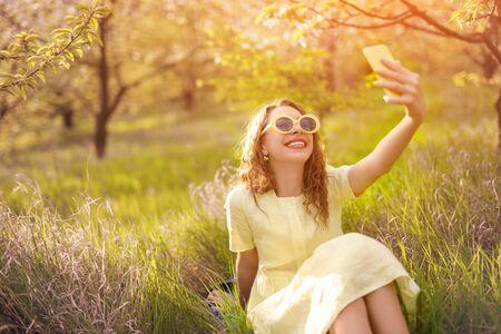 Joyful modern woman taking selfie while relaxing on grass