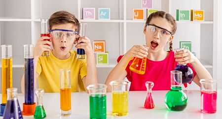 Rapturous mates making experiment with bright liquid at school