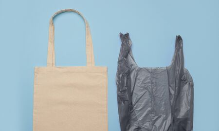 Reusable canvas bag and black plastic package Imagens