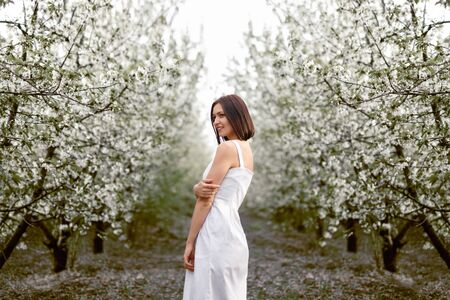Content modern woman in dress standing in blossoming spring garden Фото со стока