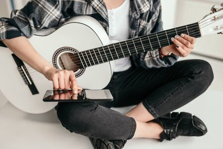 Crop woman with smartphone learning to play guitar