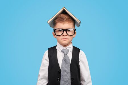 Serious schoolboy in glasses covering head with book