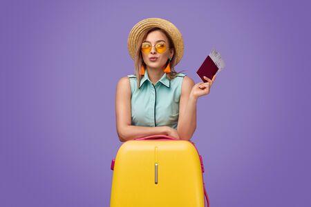 Stylish tourist leaning on suitcase