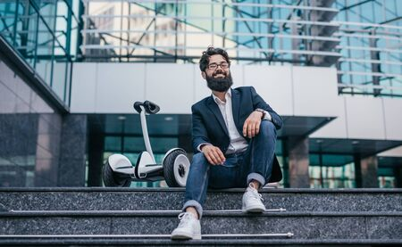 Bearded hipster resting near gyroscooter