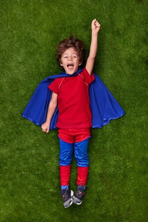 Excited superhero reaching dream on lawn
