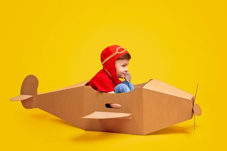 Joyful boy playing with cardboard airplane
