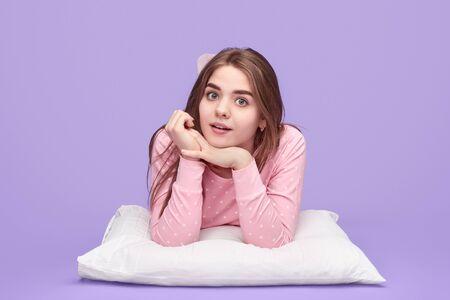 Interested teen girl lying on pillow