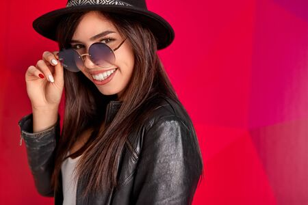 Cheerful stylish woman in sunglasses and hat smiling