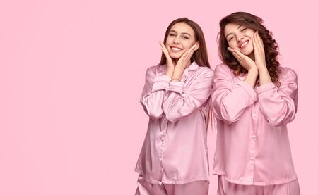 Best friends in sleepwear touching clean skin Stockfoto