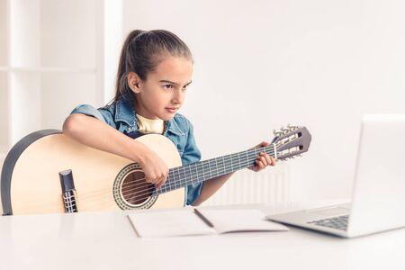 Kleines Mädchen lernt online Gitarre spielen