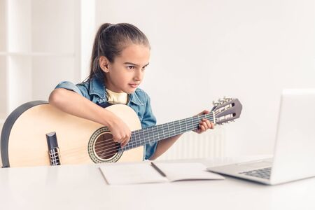 Little girl learning to play guitar online