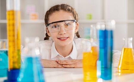 Inquisitive girl with vivid liquid in classroom