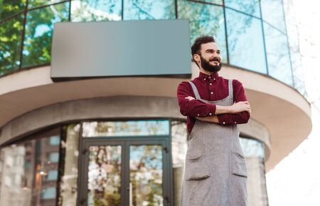 Proud owner of coffee shop standing next to empty sign