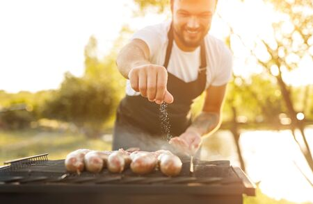 Smiling chef salting sausages on grill Stock fotó