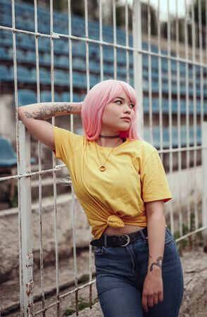 Beautiful young Asian woman with pink hair on stadium