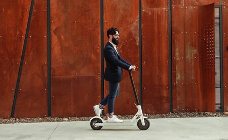 Bearded man riding electric scooter on sidewalk