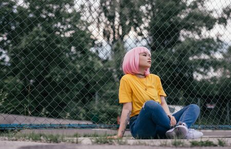 Pensive young Asian woman sitting on ground