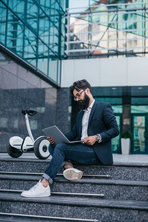 Freelancer using laptop near gyroscooter on street Stock Photo