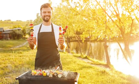 Smiling chef with grilled skewers in nature Archivio Fotografico - 130114429