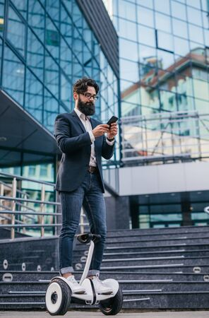 Bearded manager using smartphone on hoverboard Stock Photo