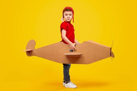 Playful boy in helmet playing with handmade cardboard plane Фото со стока