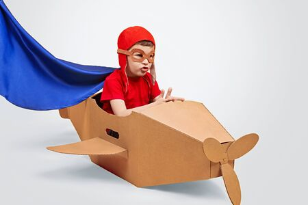 Captivated boy playing with cardboard airplane