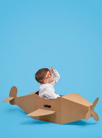 Joyful boy playing with cardboard airplane and exploring sky