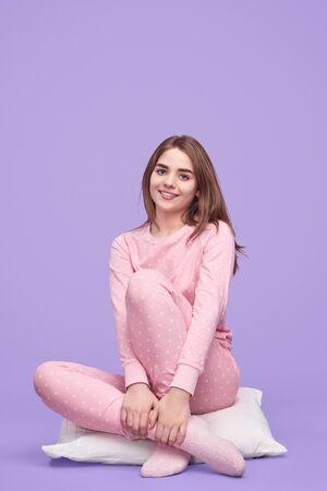 Smiling teenager sitting on pillow