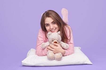 Happy teenager with teddy bear lying on pillow Imagens