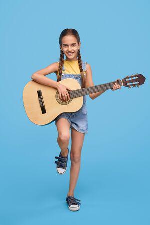 Smiling girl playing guitar and looking at camera