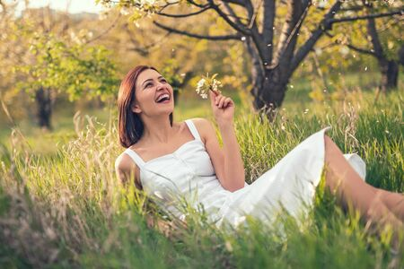 Laughing woman lying on grass in garden