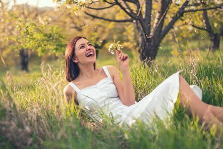 Mujer riendo tumbado sobre el césped en el jardín Foto de archivo